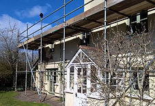Scaffolding surrounding a cream painted house with a tree in blossom in the foreground