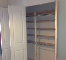 A white built in wardrobe with two shining chrome rails and bi-fold doors
