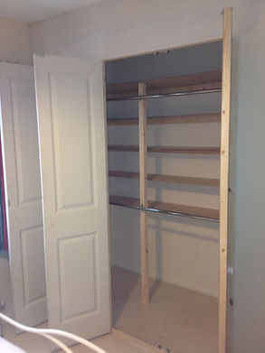 a crispi white built in wardrobe with bi-fold doors and chrome hanging rails inside