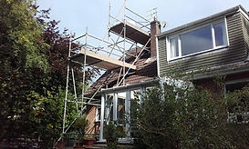 Chimney Scaffolding erected in two giant steps past a cladded dorma window of a house surrounded by green and purple shruberry