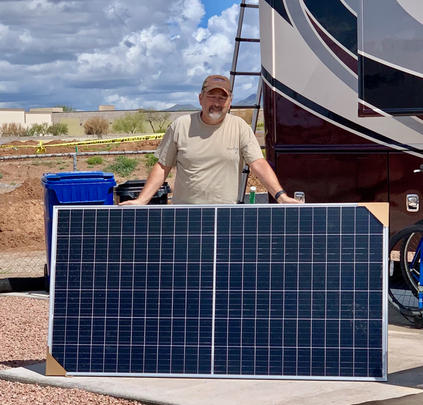 R is holding one of his 390 watt pannels that makes up his 1560   watt system. Together with his 400 amp hours of Battle Born batteries, he is all set.  March 2020