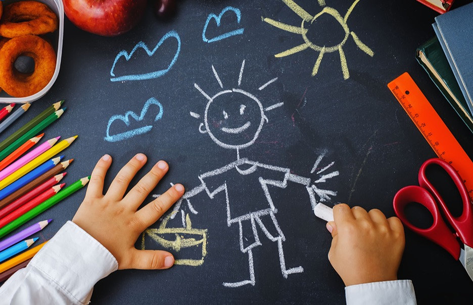 childrens-hands-writing-on-a-blackboard-