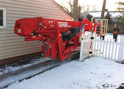 Teupen tracked lift being transported through a standard fence gate.