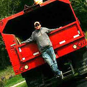 Andy Wiley standing on the back bumper of a truck.