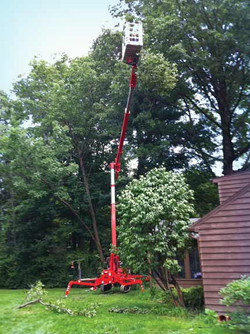 Teupen tracked lift extending above the height of a two-story house.