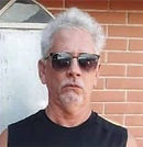 Álvaro Souza. Cabelos brancos, pele clara, óculos escuros, cavanhaque e camiseta preta.