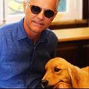 Carlos e sua cão guia Jade. Carlos sorrindo, camisa azul e óculos escuros. Jade com pelos dourados.