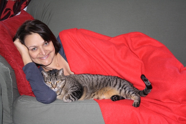 Marriette Smith, cuddling with her own cat on the couch