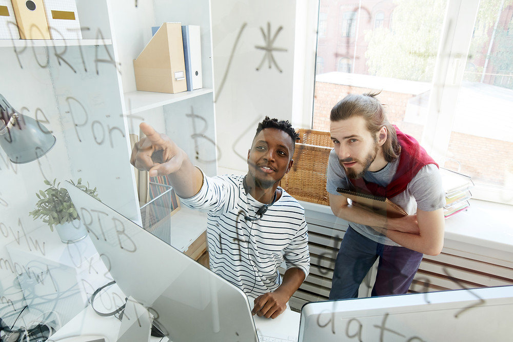 Men pointing the glass board with computer in front of them