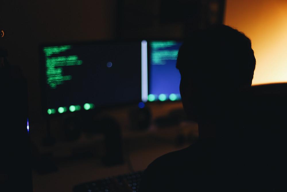 Pria menatap layar komputer untuk mengawasi dan meminimalkan Risiko Keamanan Pada Automasi