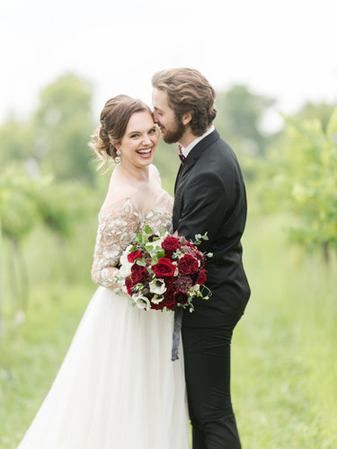 Smiling bride and groom with deep red bo