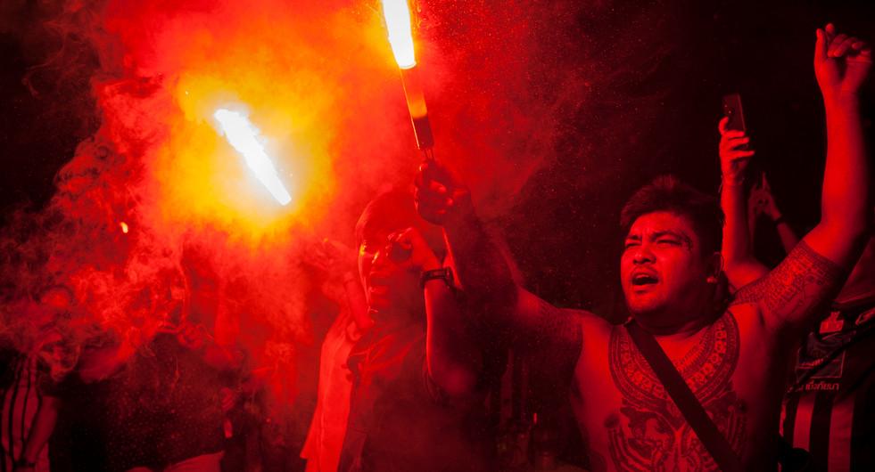 Fans light up flares outside the PAT Stadium. Bangkok, Thailand.