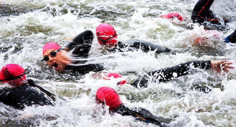 London Triathlon participants swim in the Royal Victoria Docks. London, UK.