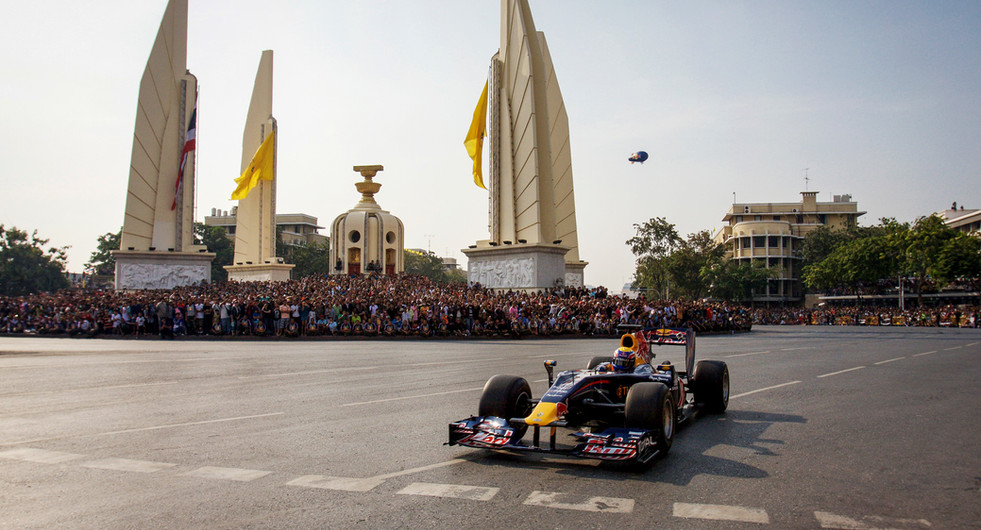 Mark Webber of Red Bull F1 Racing drives the RB6 car past Democracy Monument. Bangkok, Thailand.