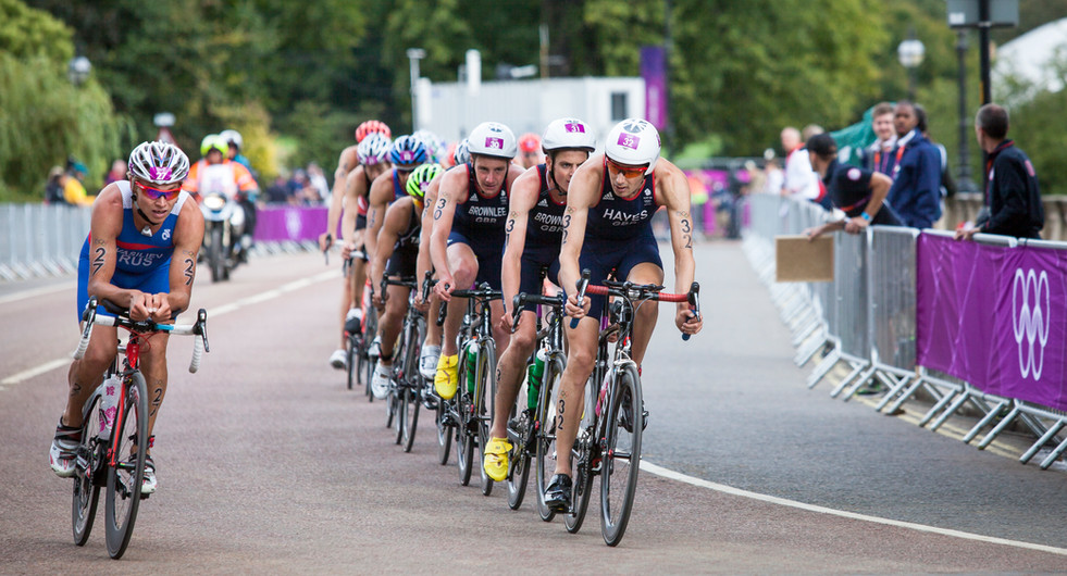 Ivan Vasiliev attempts to overtake Stuart Hayes and the pack during the London 2012 Olympics Men's Triathlon event at Hyde Park. London, UK.