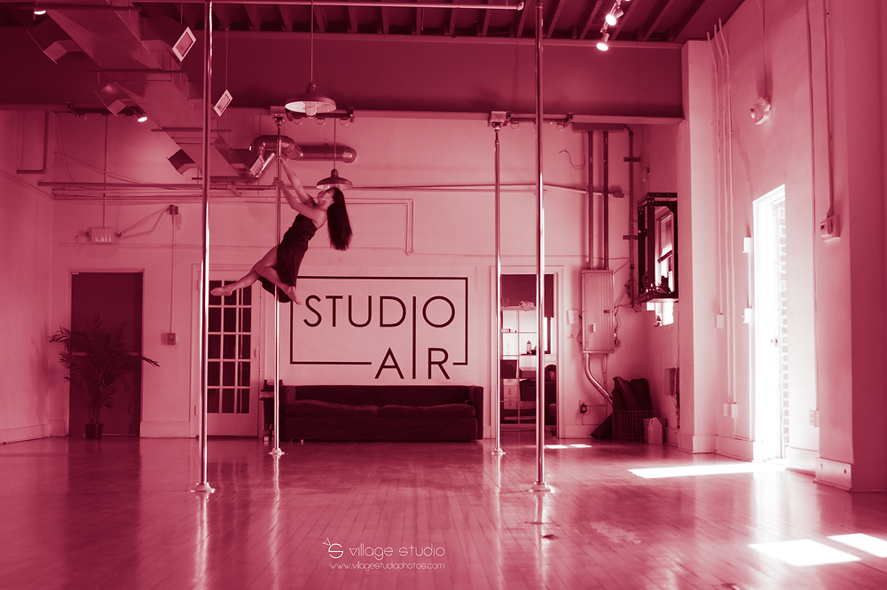 Owner of Studio Air, Linda Tsuei, wearing a mask and pole dancing by Village Studio
