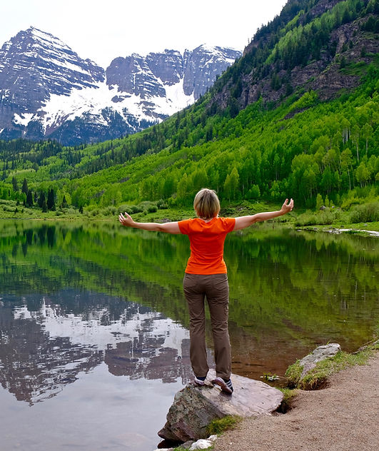 Woman by water enjoying fresh air and nature