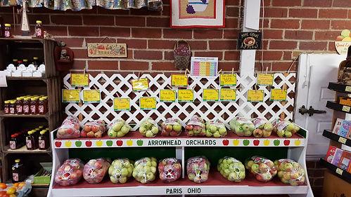 Lattig work & signage on shelves of bagged apple varieties.
