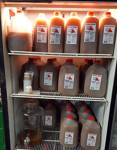Apple cider jugs in the farm market refrigerator.