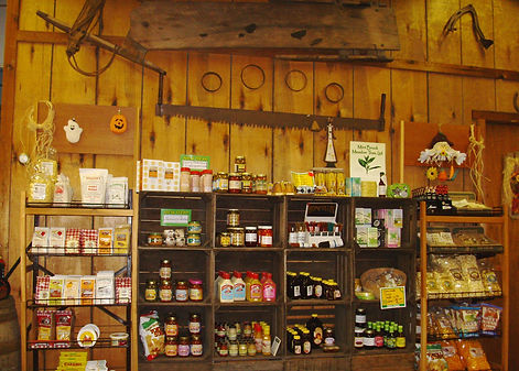 Farm market wall of jams & jellies. Antiques hanging on wall.