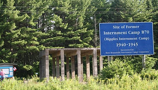 Image showing concrete base of former water tower and large sign at the site of former Internment Camp B/70, Ripples New Brunswick (30km East of Fredericton, New Brunswick).