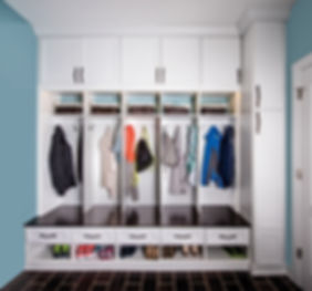 Custo built mud room with bench seating, show stoage, cabinets and pantry in whte