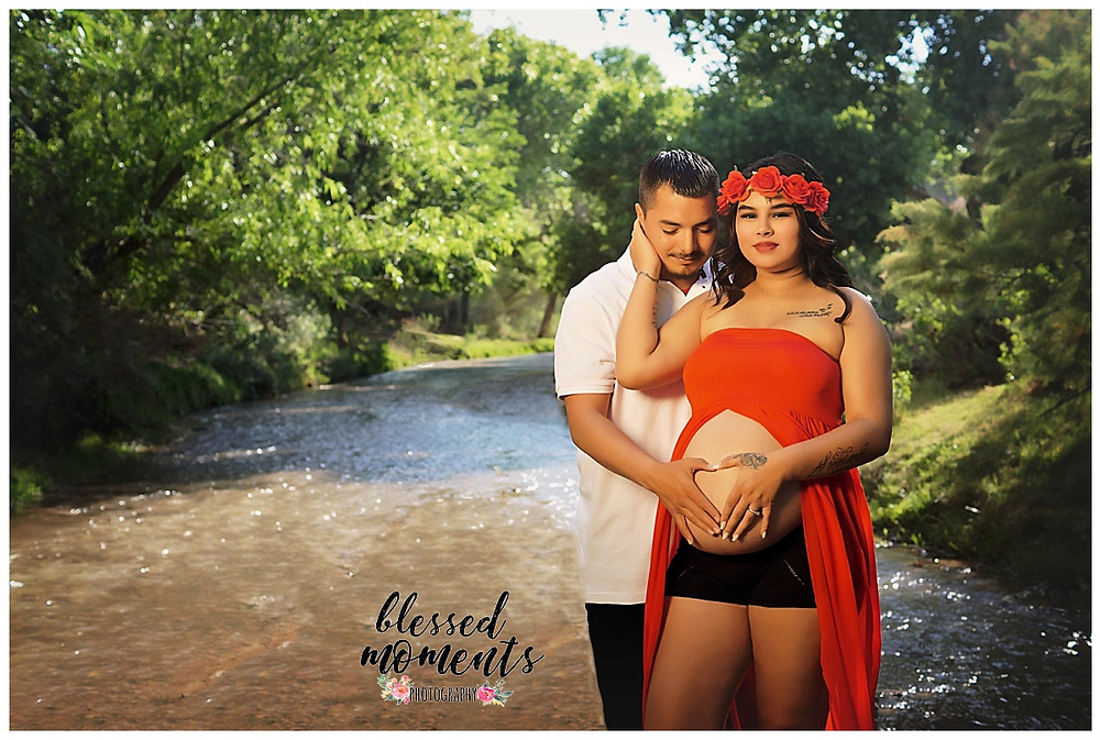 Maternity photos at Tularosa Creek with mama wearing a red maternity gown with her proud man holding her.