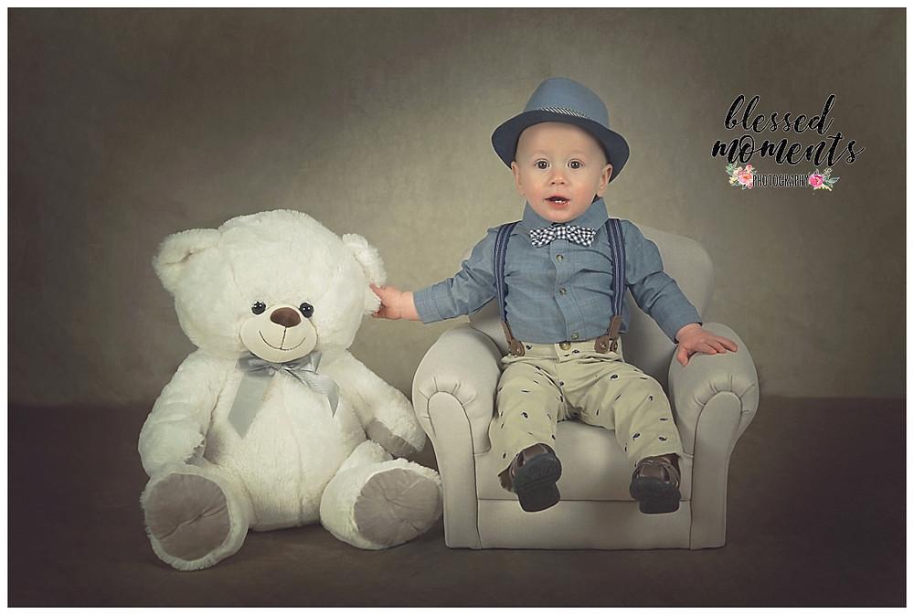 1 year old boy sitting in grey chair wearing denim shirt and hat.