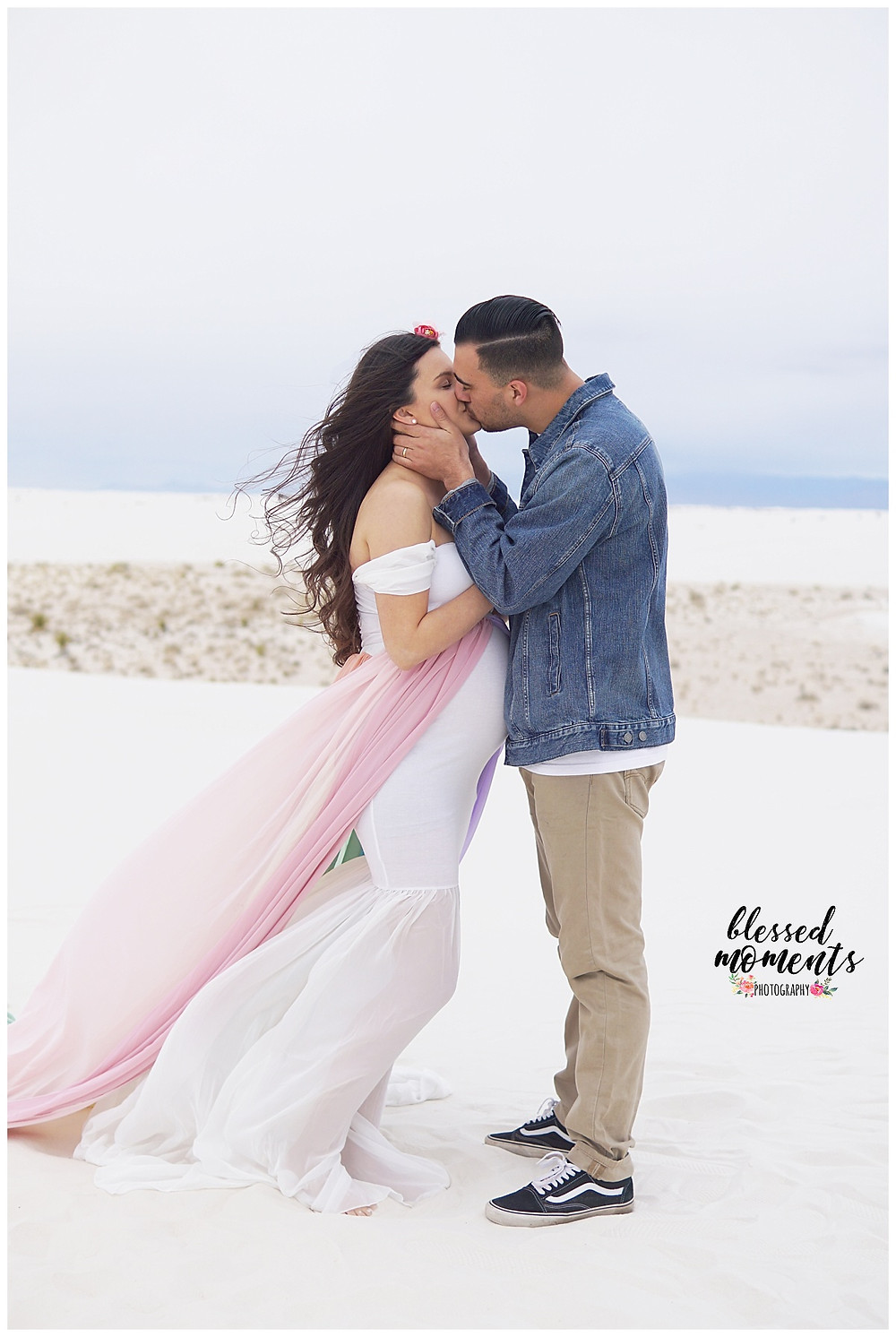Husband embracing pregnant wife with a kiss at White Sands