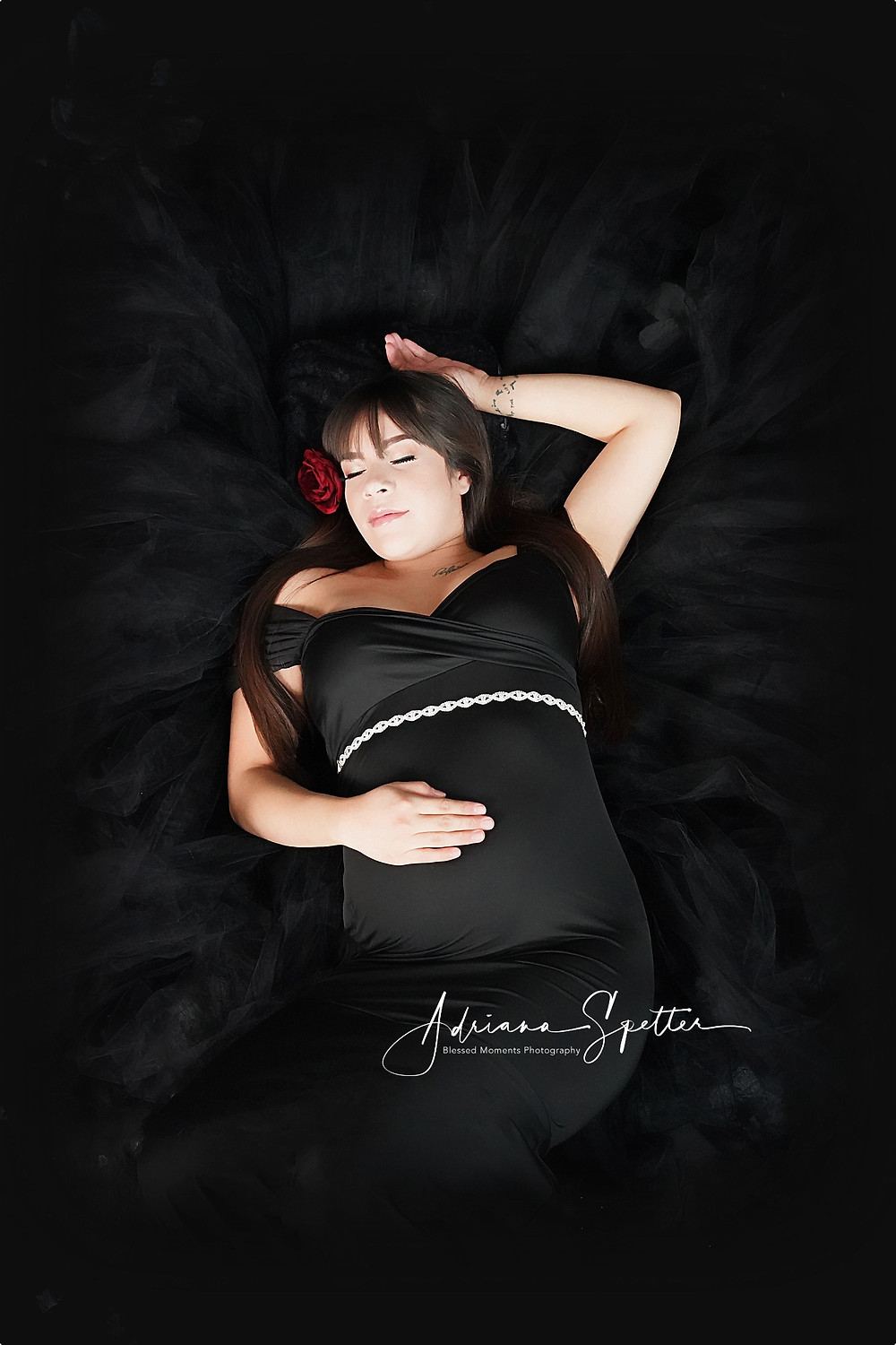 Beautiful expecting mother laying down in black fabric while wearing a black maternity gown.  Her head is tilted slight to her right with her hair adorned with a red flower.  Photo done in Blessed Moments Photography Studio in Alamogordo.
