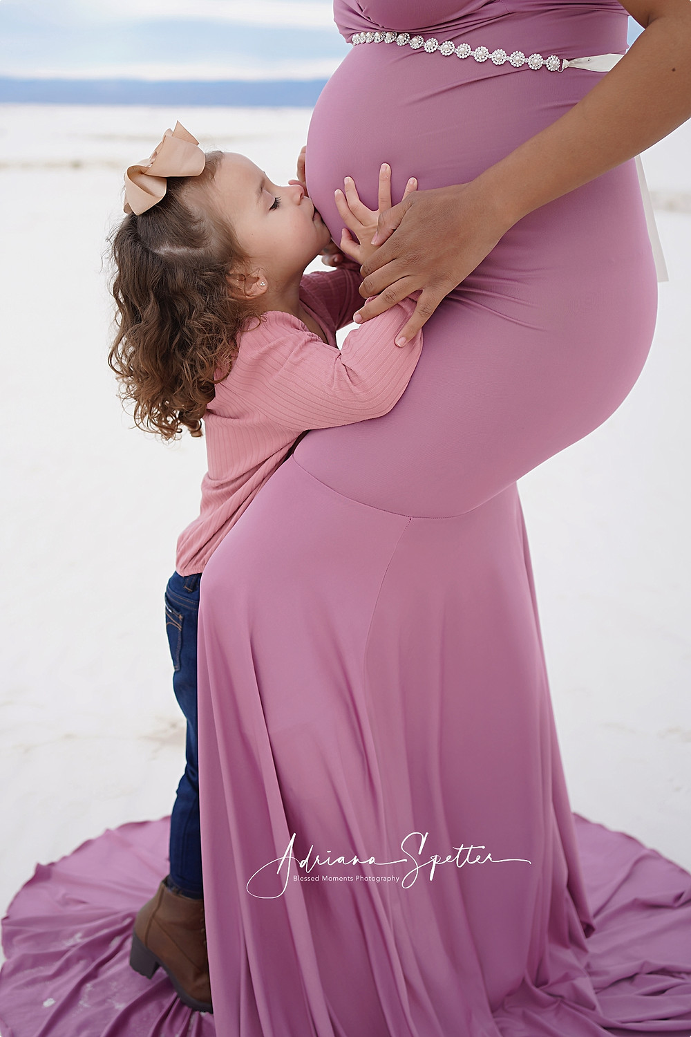 Little girl kissing her mama's pregnant belly