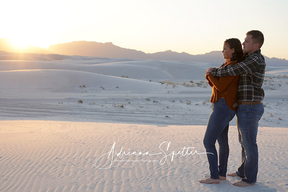 A man embracing his fiance on an engagement photo session at White Sands National Monument