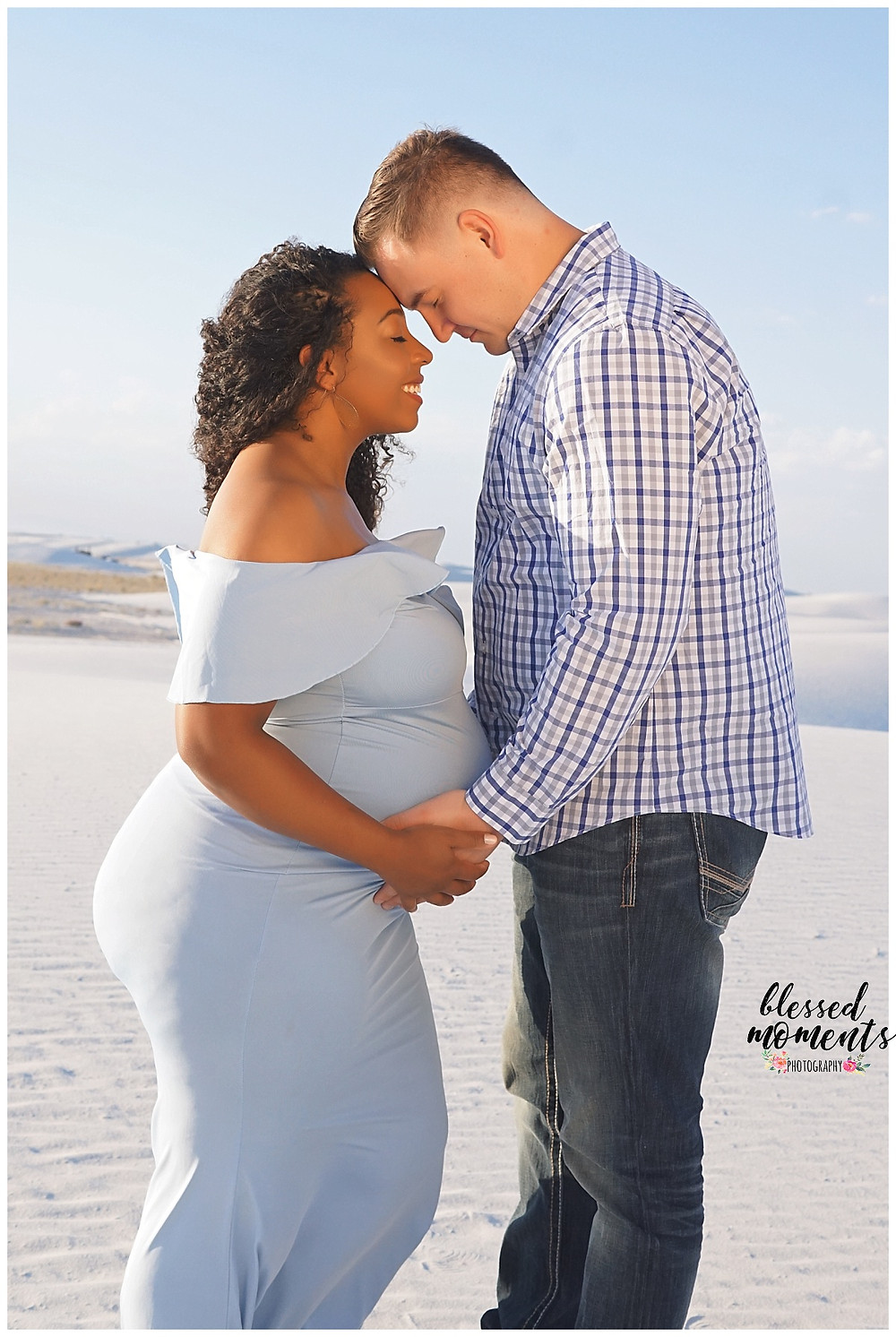 Proud future mama and papa embracing at White Sands for Maternity photos