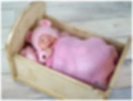 Newborn girl photos in little bed wrapped in pink wrap