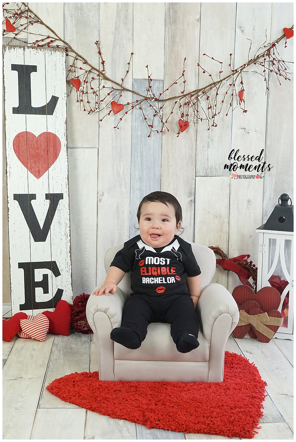 Young baby boy sitting on a grey mini soft for Valentines mini session with white backdrop