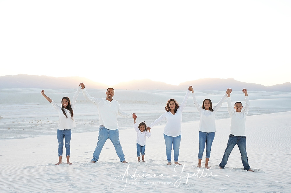 Family photo at white sands with mom, dad, 3 daughters and a son all holding up their hands wearing a white shirt and blue jeans.