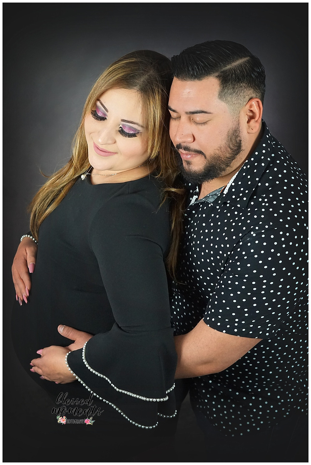 Maternity photography shot with husband in studio against dark background and black outfit.