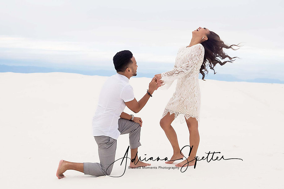 White Sands Engagement photo with man proposing and woman leaning back and laughing in excitement