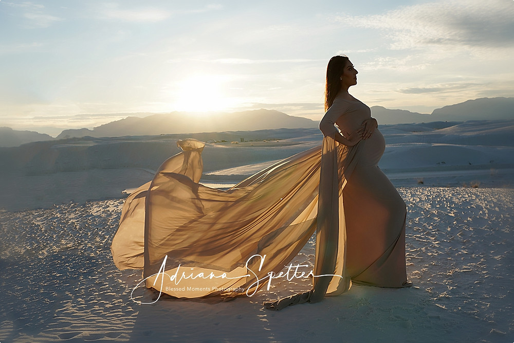 Beautiful Latina mama wearing a Tuape Maternity gown with the sun setting behind her at White Sands National Park.