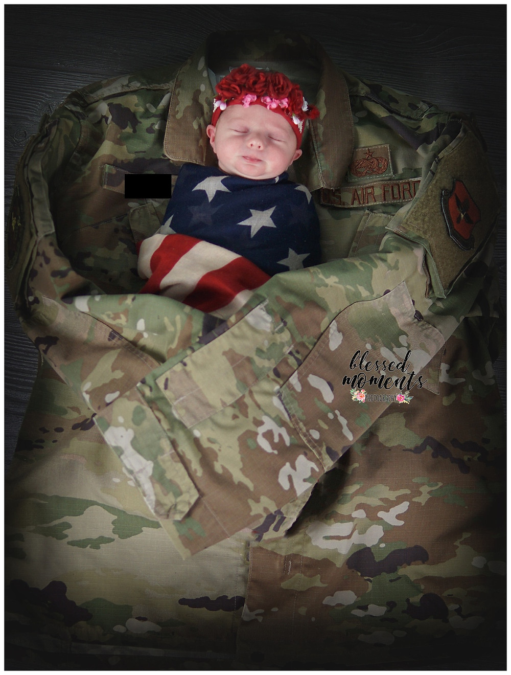 newborn baby wrapped in a flag colored scarf and laying in a military uniform