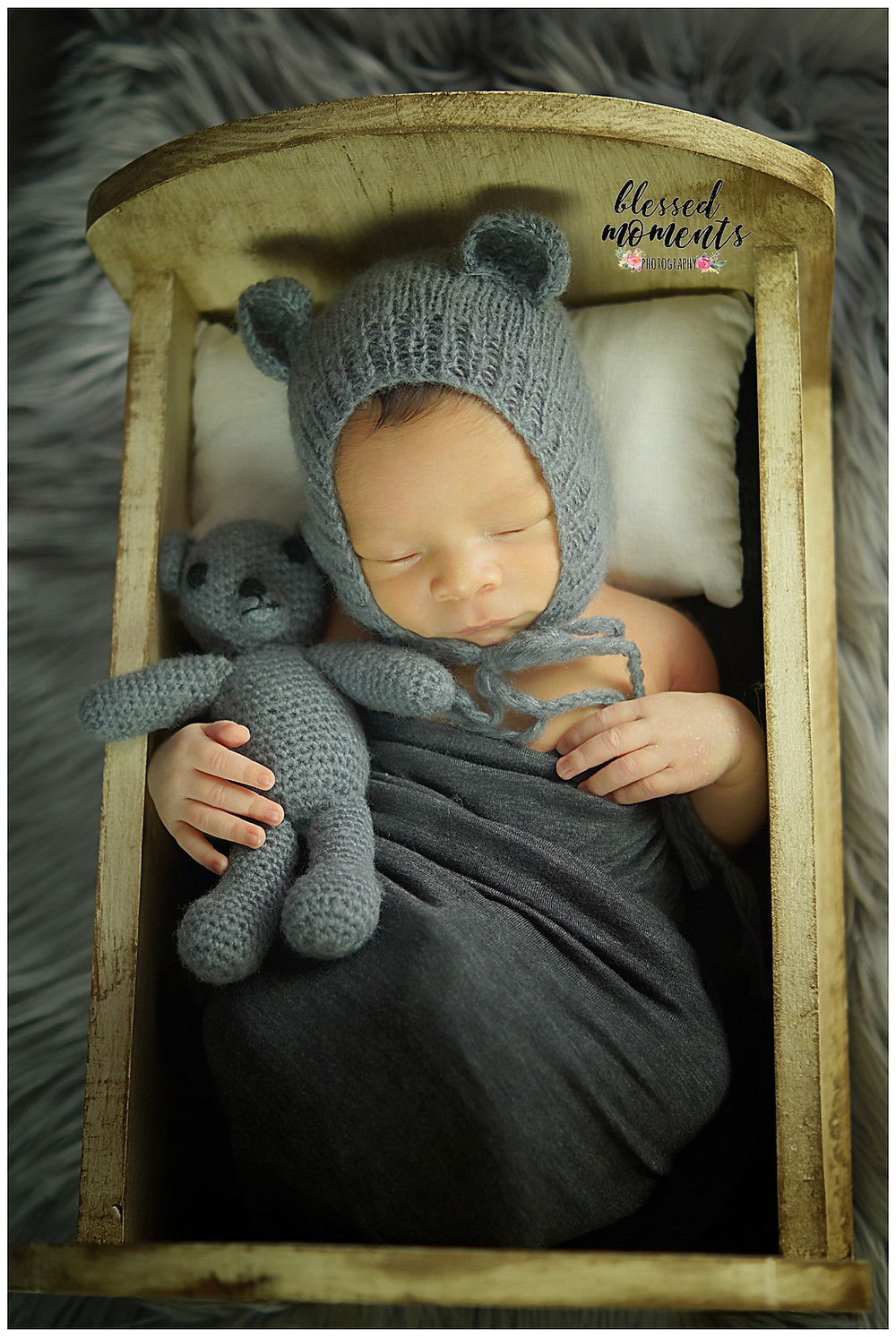 newborn baby boy with grey bear bonnet while holding grey bear and laying in a wooden bed.