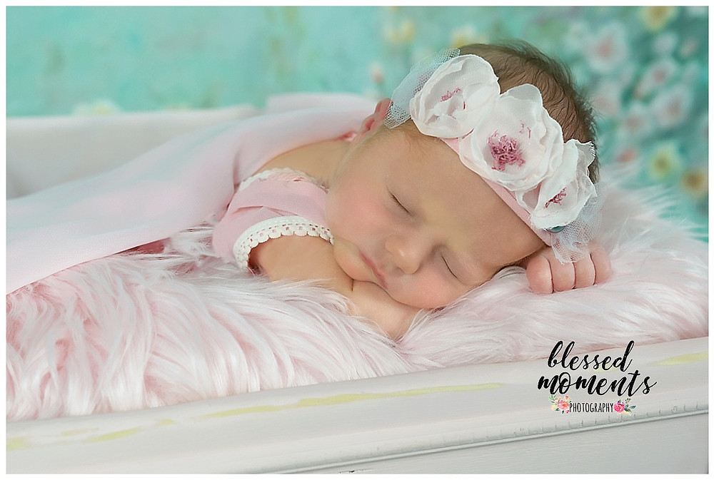 Newborn baby in pink outfit, laying on pink flokati with a floral headband