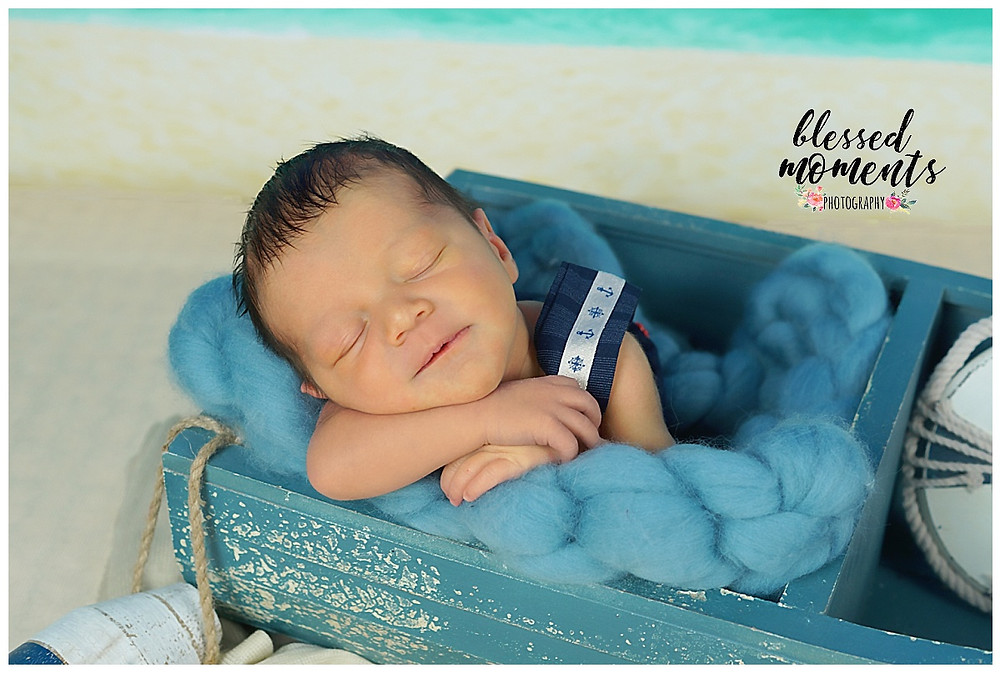Close up of newborn photo with little boy in sailor outfit sleeping in a boat.