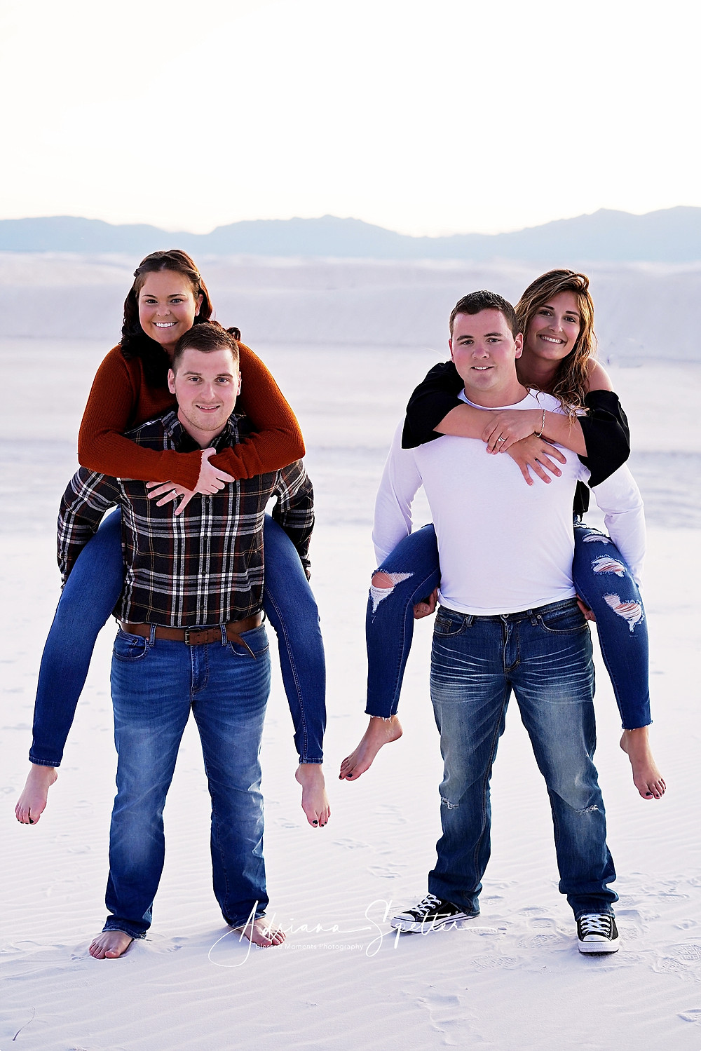 Two couples at White Sands National Monument with the men carrying the women on their back.