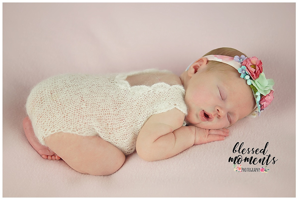 Newborn photo of baby girl in pink jumper and floral crown