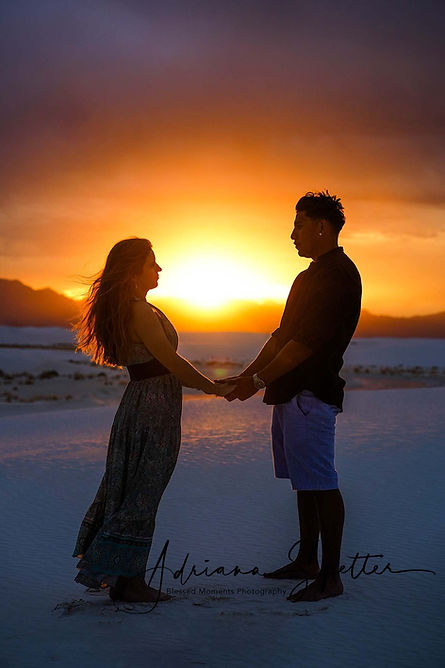 White Sands Couple photography with couple staring into each others eyes at White Sands National Park with the sun setting behind them.