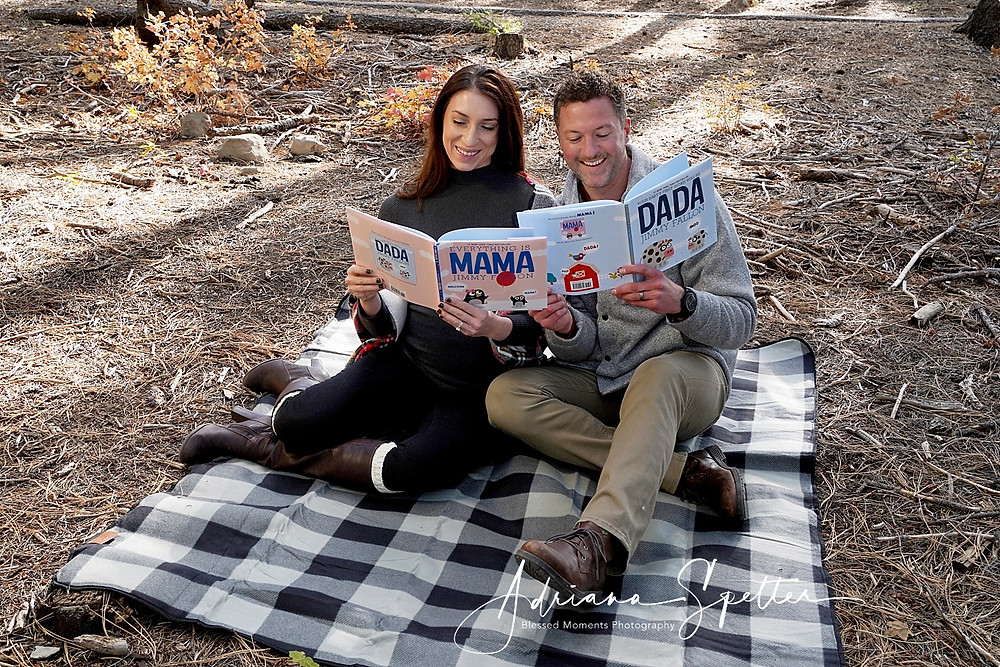 Couple reading Jimmy Fallons children books while sitting on a blanket.