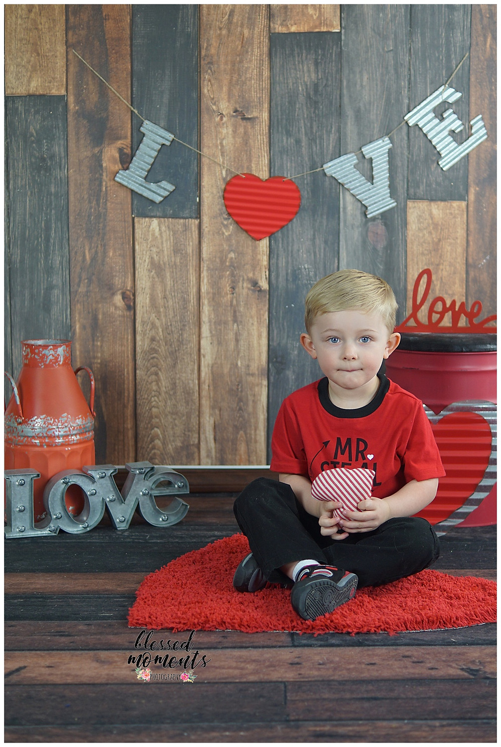 Valentine mini photo session with little boy sitting on dark wood backdrop and floor.