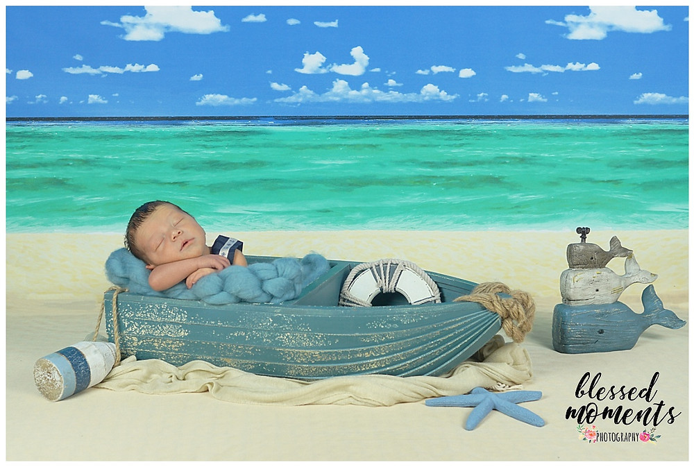 Newborn photo session with little boy in sailor outfit sleeping in a boat with Whales