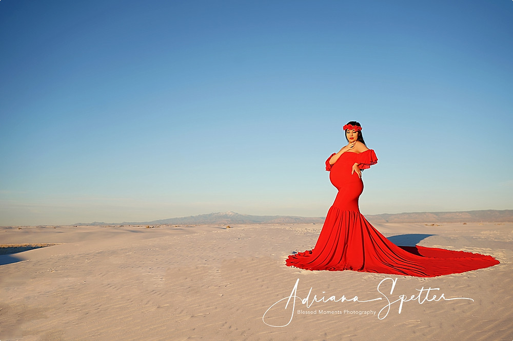 Scenic photo of White Sands National Park with expecting mother in red dress